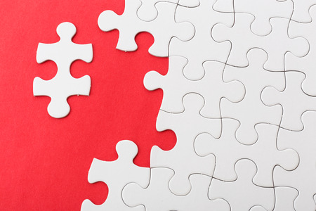 Incompleted white puzzle on red background photo