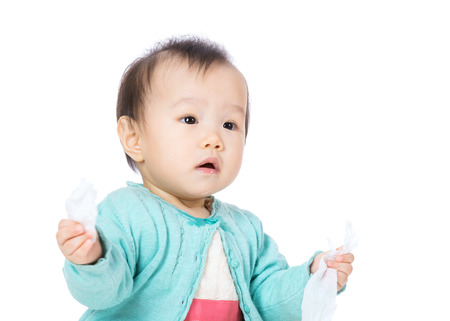 Baby girl with tissue on hand photo