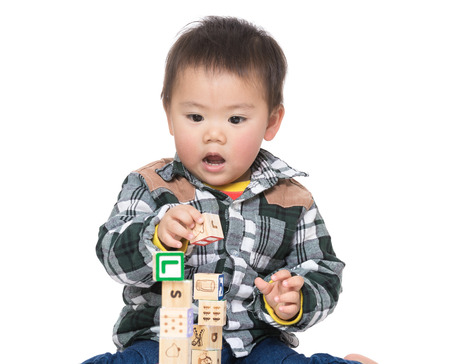 tight focus: Asia baby boy play wooden toy block