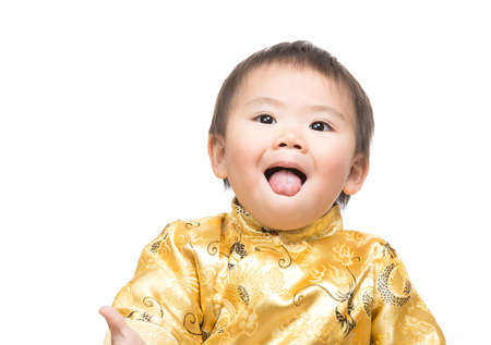 Chinese baby boy with traditional costume shiowing tongue photo
