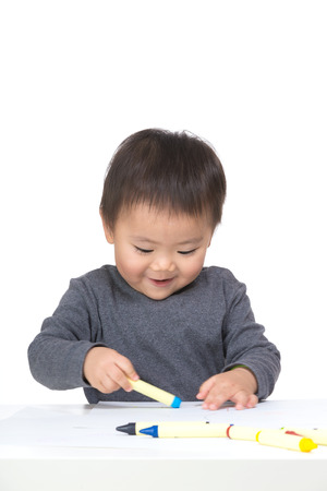 Kid drawing with crayon photo