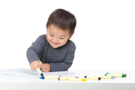 Asian boy drawing with crayon photo
