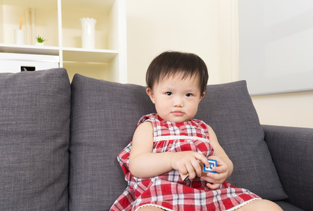 Asian baby girl play with toy block and sitting on sofa photo
