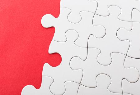 Unfinished puzzle over red background Reklamní fotografie