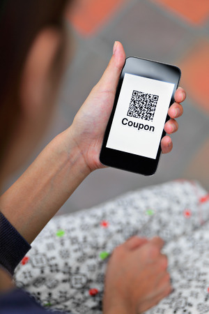 Woman hand holding mobile phone with QR code coupon photo