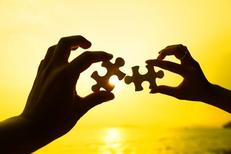 piezas de rompecabezas: Dos manos tratando de conectar las piezas del rompecabezas con el fondo de la puesta del sol Foto de archivo