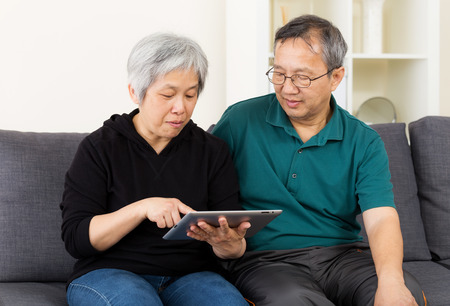 Asia old couple using tablet photo