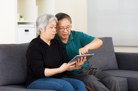 Asian old couple using tablet together photo