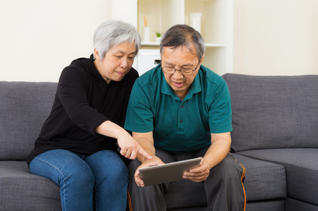 Senior couple watching on tablet at home photo