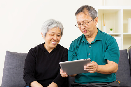 Asian couple looking at tablet together photo