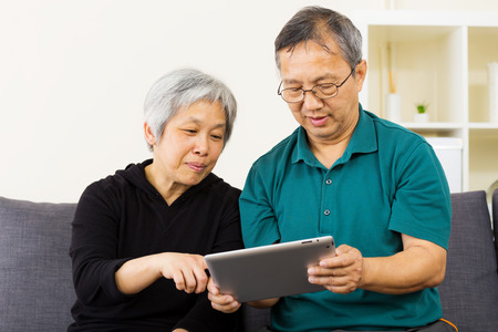 Asian couple using tablet together at home photo