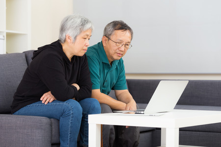 Elderly couple using laptop computer at home photo