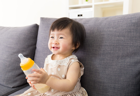 Asia baby holding milk bottle at home