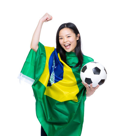 Excited asian woman draped with Brazil flag and holding soccer ball photo
