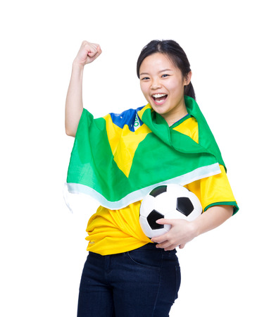 Excited asia woman draped with Brazil flag and holding soccer ball photo