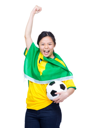 Excited asia female football supporter holding soccer ball photo
