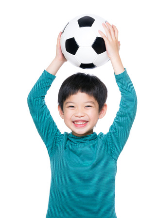 Asia little boy holding up with soccer ball photo
