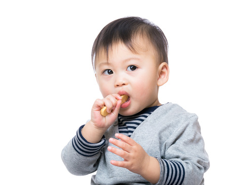 Asian baby boy eating biscuit