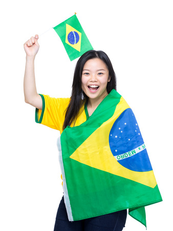 Excited asian woman holding and draping with Brazil flag photo