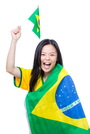 Excited asia female football supporter holding small Brazil flag photo