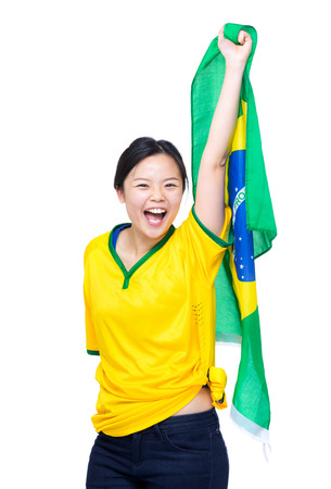 Asia woman with yellow football clothes and holding up Brazil flag photo
