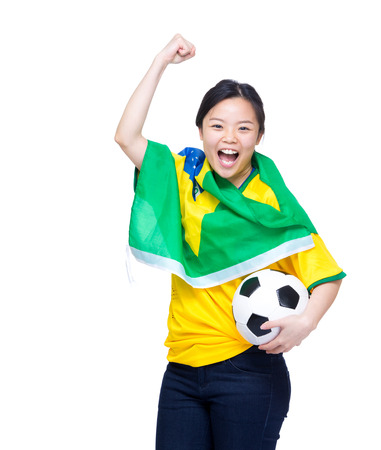 Excited asian woman draped with Brazil flag and holding soccer ball Stock Photo - 27101251