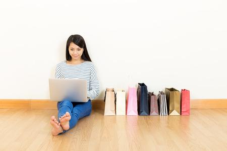 white laptop: Donna di shopping online a casa