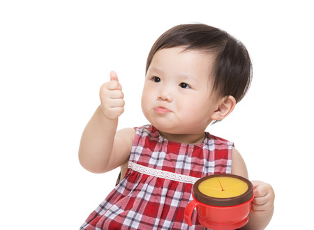Asian baby girl with snack box and thumb up Stock Photo