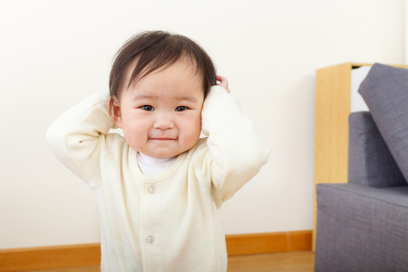 Asian baby girl hand cover her ear photo