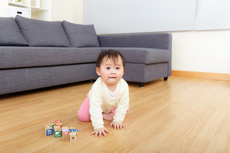 Asian baby girl play wooden toy block