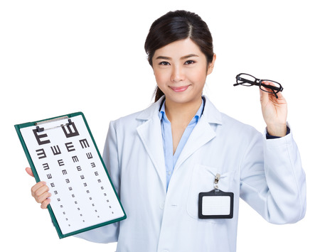 Optometrist showing eye exam chart and holding glasses photo
