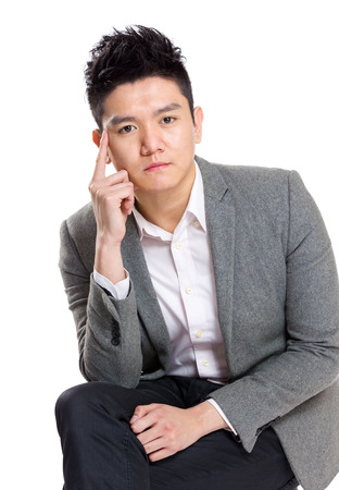Asian businessman thinking and sitting on chair photo