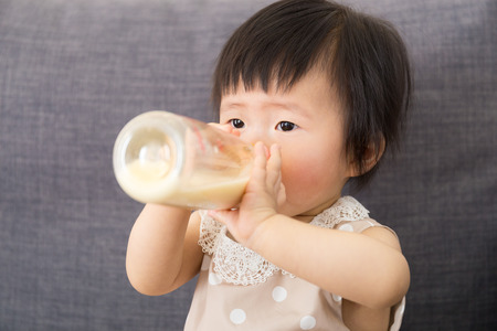 Asian baby girl feeding with milk bottle photo