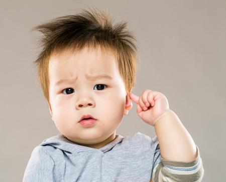아기 소년 그의 귀를 만지지