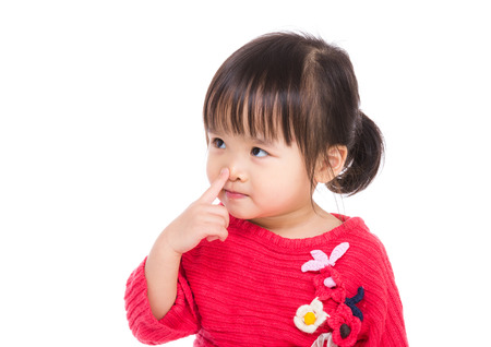 pointing finger up: Asia little girl touch her nose