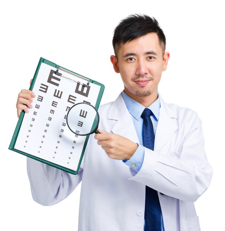 Male doctor holding optometry chart and magnifying glass photo