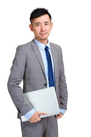 Businessman holding laptop computer photo