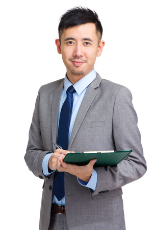 Businessman making notes on clipboard photo