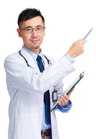 Asian doctor holding clipboard and pen pointing up photo