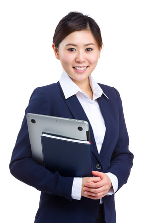 Businesswoman holding laptop and notebook photo