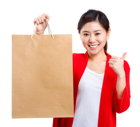 Shopping young woman show thumb up with bag photo