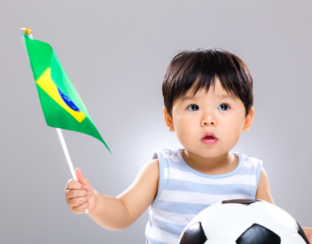 Baby son holding flag and soccer ball photo