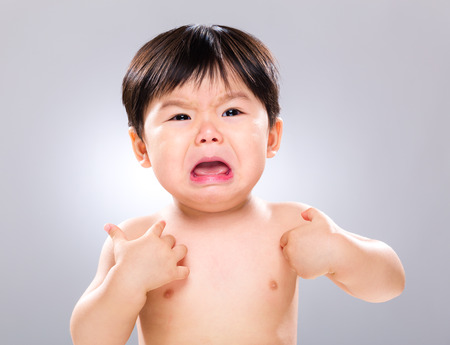 scratching head: Crying baby with scratching his body