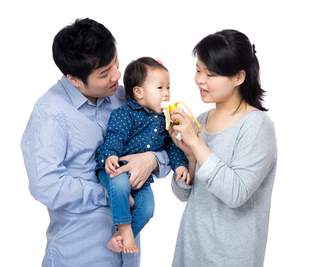 Mother give banana to daughter in asian family photo