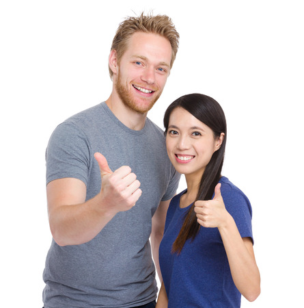 Friendship of caucasian and asian with thumb up photo