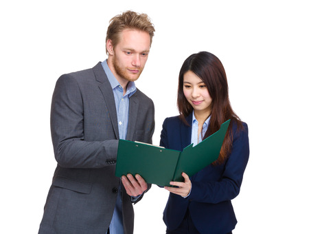 togther: Business man and woman looking at clipboard