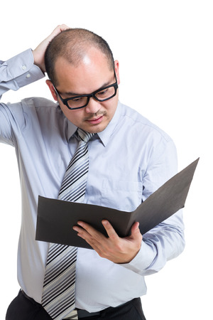 Stressed businessman and looking at file pad photo