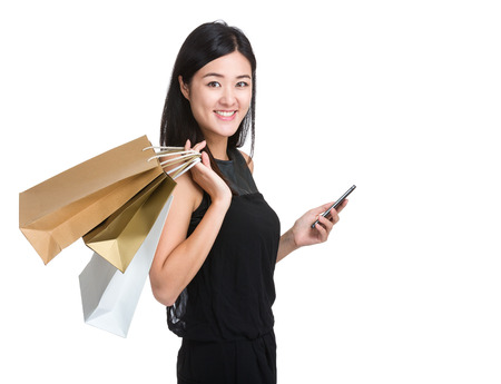 Asian woman with shopping bag and mobile phone photo