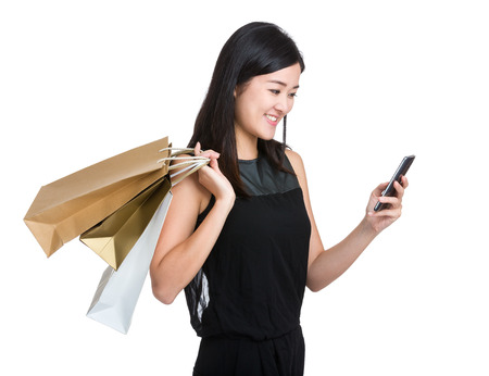 Woman hold shopping bag and look at ceelphone photo