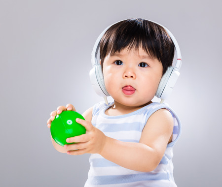 Baby hold plastic ball with headphone photo